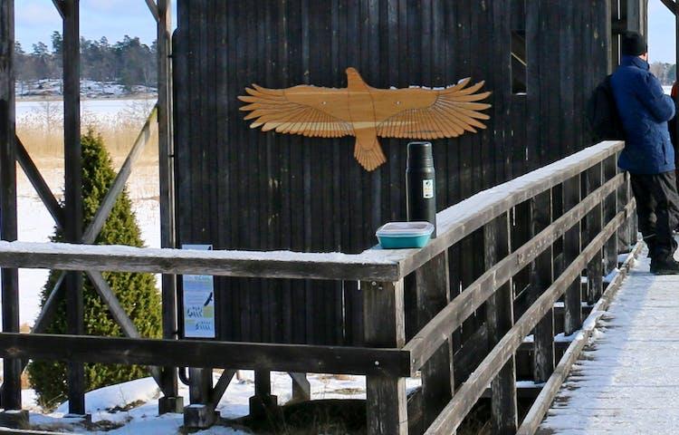 Silhuett i trä av havsörn sitter på en vägg utomhus.