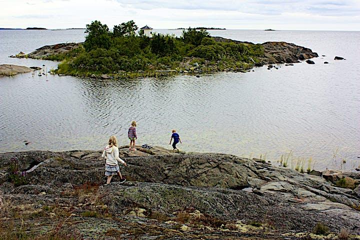 Tre barn går på en klipphäll vid havet. I bakgrunden finns en liten ö med många buskar.