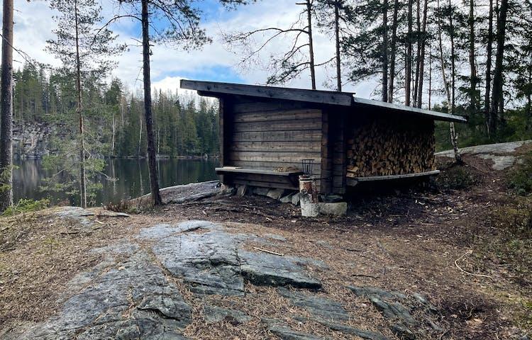 Knuttimrad liten byggnad vid en sjö.