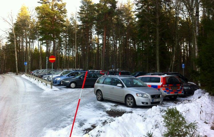 En grusplan med många parkerade bilar.
