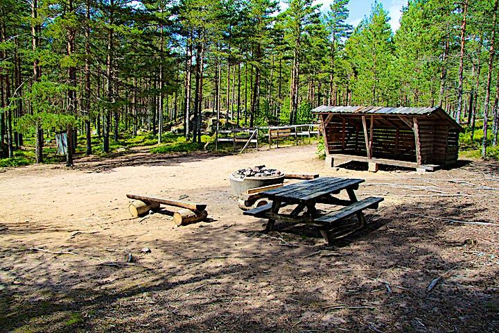Rastplats med bord med bänkar, bänk, eldstad och ett vindskydd.