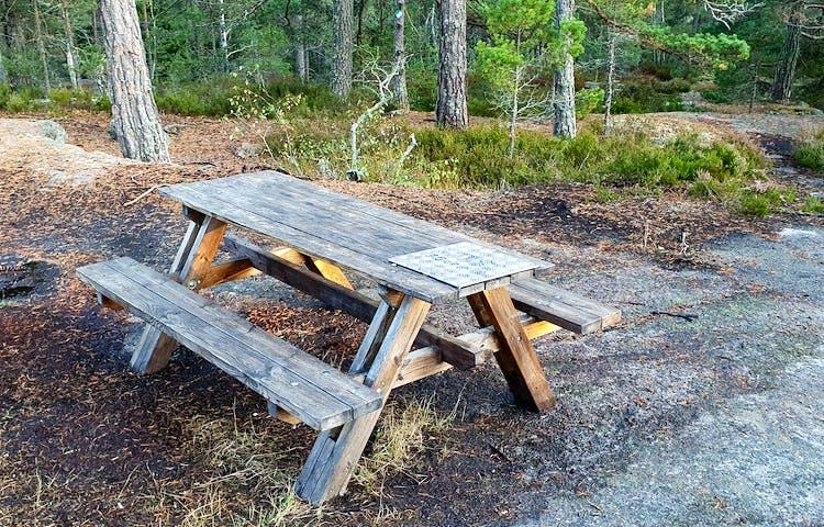Ett bord med sittplatser står på berghällen.