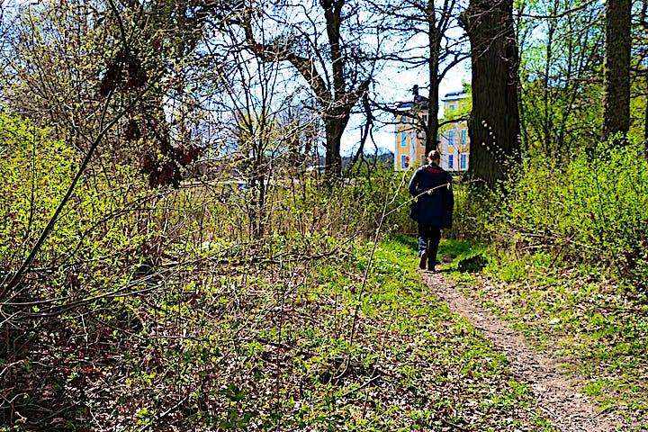 En person går bortåt på stigen, i bakgrunden syns Strömsholms slott.