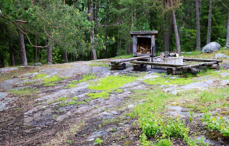 Rastplats på klippor med eldstad, vedförråd och bänkar.