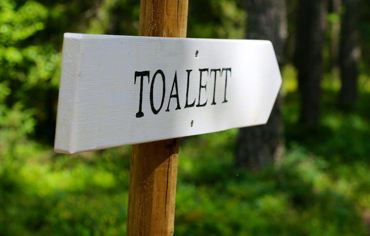 Vit skylt med text: Toalett.
