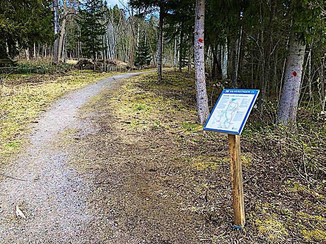 Informationstavla längs grusad stig.