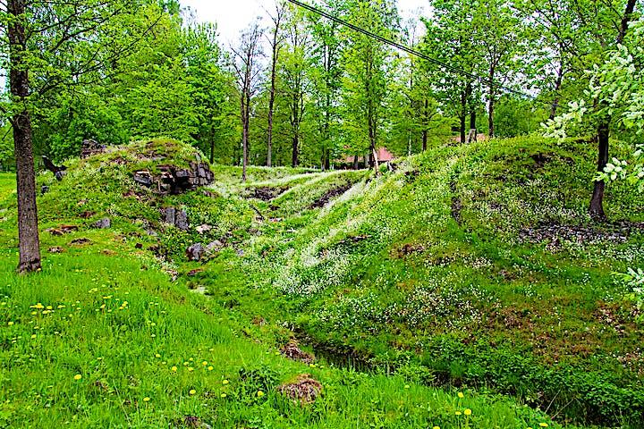 I den kuperade och grönskande terrängen syns rester av en grund.