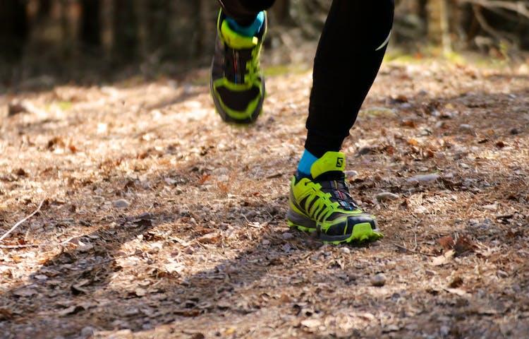 Närbild på en joggande persons träningsskor som sätter i marken.