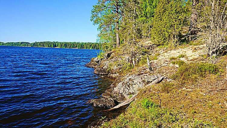 En sjö till vänster, till höger klippor som går ner i vattnet och lite skog.