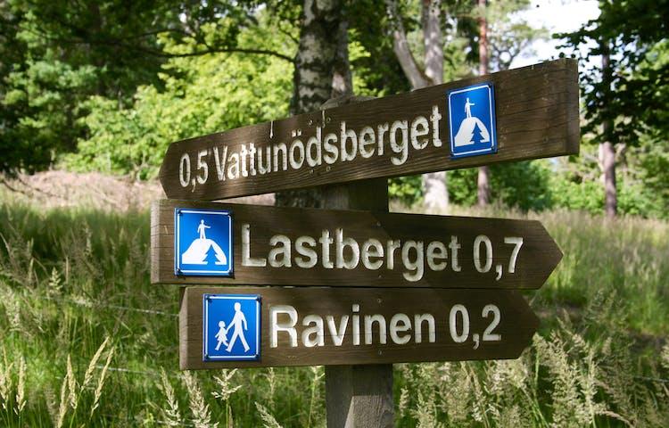 En vägvisare pekar mot Vattunödsberget, Lastberget och Ravinen.