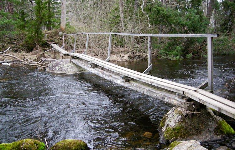 En mycket smal bro med ett handräcke på ena sidan går över ett vattendrag.