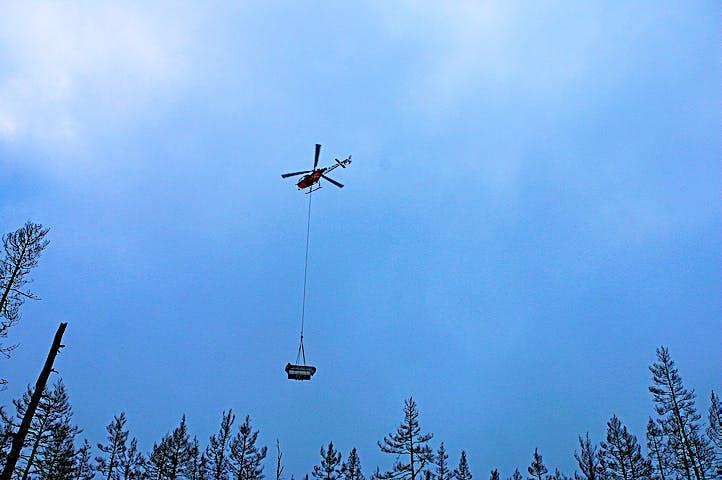 Helikopter flyger med last över trädtopparna på Grävlingsberget.