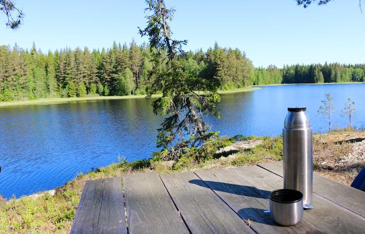 Ett träbord med en termos som står på en klippa i en skog med en sjö i bakgrunden.