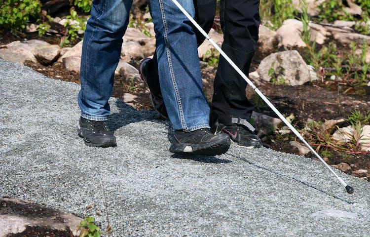 Fötterna av två personer, den ena med käpp för synskadad, går på grusad stig.