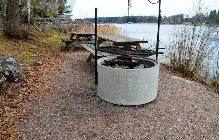 En grillplats med två grillgaller ovanpå står på grusad yta vid vattnet. Bakom grillplatser finns två bänkbord.