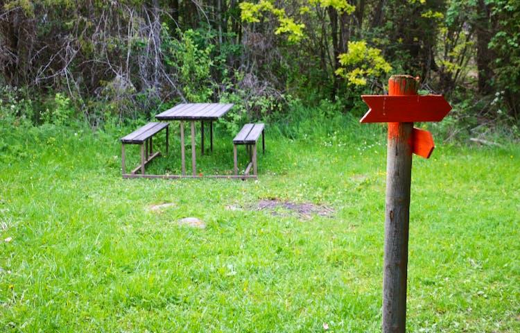 Ett bord med bänkar står längs leden. Orange pilar på en stolpe visar vägen.