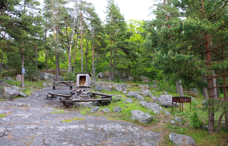 Rastplats med eldstad, vedförråd och bord och bänkar. Rastplatsen ligger på en klippa.