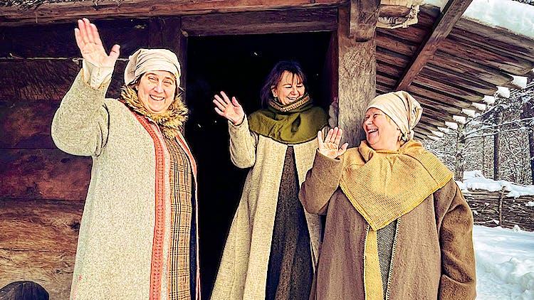 Tre kvinnor i historiska kläder ler och vinkar mot kameran. De står utanför ett trähus.