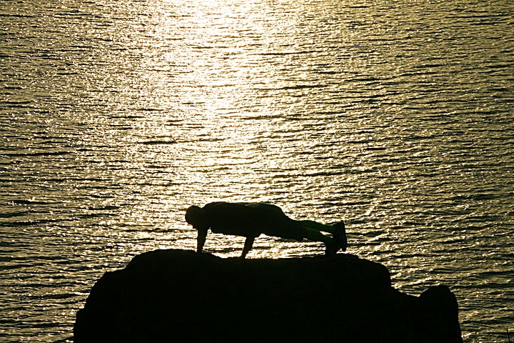 Man gör armhävningar på klipporna. Vattnet glittrar av solens sken.