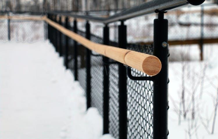 Närbild på staket med ledstänger i två olika höjder.
