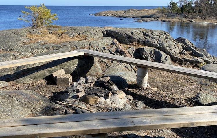 En låg eldstad med tre stockbänkar ovanpå stora stenar. Det är väldigt ojämnt och stenigt på marken runtom grillplatsen.
