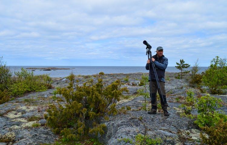 En man står på en stenhäll och håller i en tubkikare. I bakgrunden är det hav.