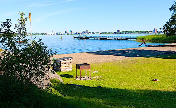 Sandstrand med grill, rutschkana och en lång brygga. I bakgrunden skymtas Västerås.