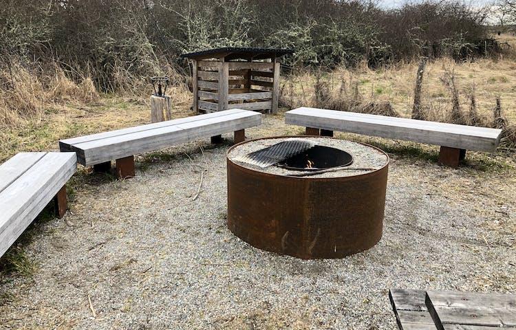 En rund grillplats med tre träbänkar runt omkring. Ett vedskjul i bakgrunden.