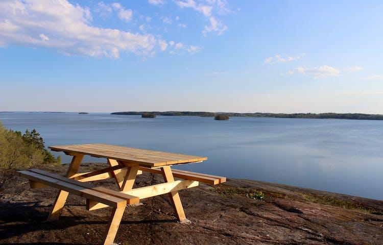 Ett bänkbord står på höga klippor med utsikt över vatten och öar.