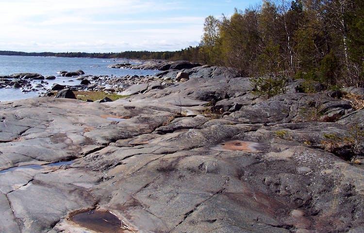 Släta men mycket ojämna klippor leder ner till havet.