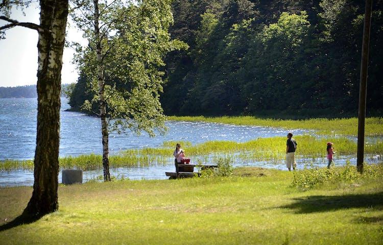 En familj vid ett picknickbord vid vattnet.