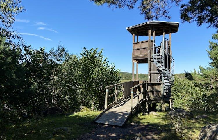 En träspång leder fram till ett torn, byggt i trä och format som ett lusthus i två våningar
