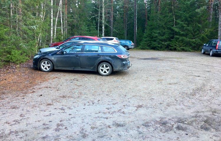En grusplan omgiven av skog och sex bilar som står parkerade längs kanten.