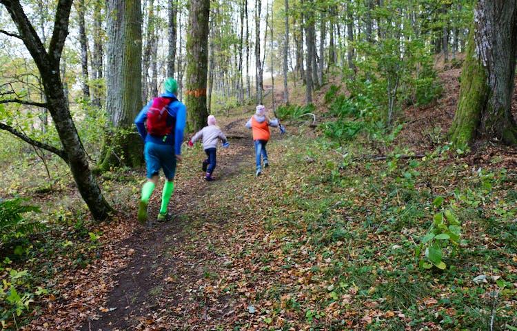 En vuxen person och två barn springer uppför en stig. Intill stigen finns ett orangemarkerat träd.