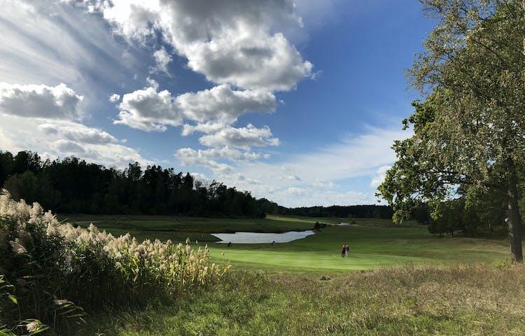 Golfbana med två spelare på greenen.