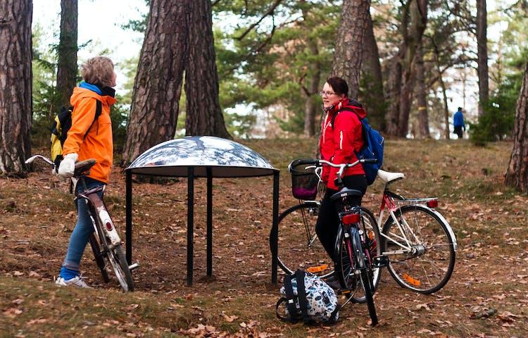 Två vuxna står vid en metallskulptur i skogen med tre cyklar. I bakgrunden går en person genom skogen.