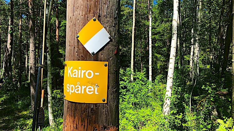 En gul skylt på en stolpe. Vit text på skylten: Kairospåret.