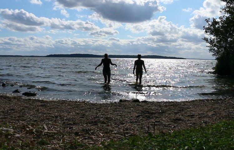 Två personer på väg ut i vattnet för att bada.