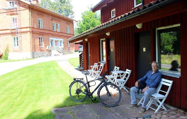 En man vilar på en bänk med en cykel bredvid sig, utanför boendet vid Kungskvarnen i Borgvik