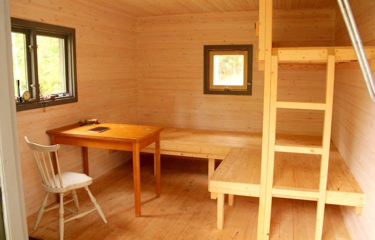 Inne i stugan: stol, bord, två britsar och en överslaf