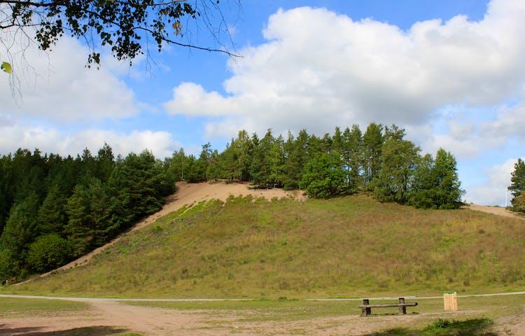 En mycket brant och hög backe med skog på toppen. Nedanför är det en stor öppen gräsyta med ett bänkbord på.