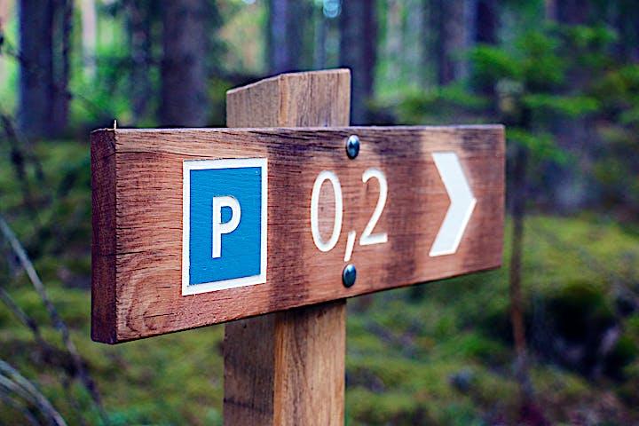 Skylt längs led som visar riktning och avstånd till parkering.
