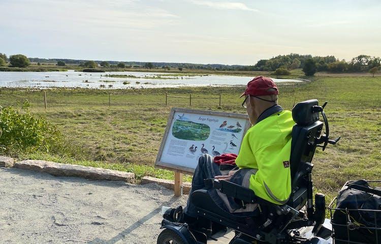 En man i rullstol står på vid en informationstavla på en grusplan. Runt grusplanen finns höga kanter av sten. Framför planen syns våtmark och vatten.