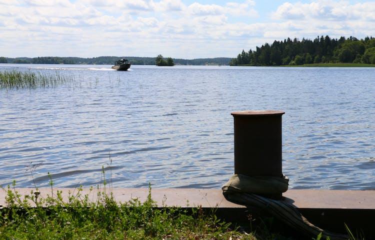 Järnstolpe för förtöjning av båt. På vattnet kommer en motorbåt in mot land.