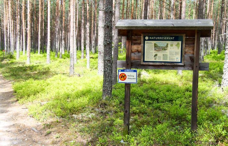 Informationstavla och en skylt som visar att ridning är förbjuden i naturreservatet.