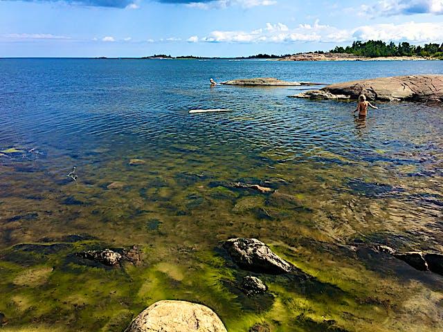 I en vik badar två personer. Det är långgrunt och genom vattnet ser man att botten är mycket stenig och ojämn.