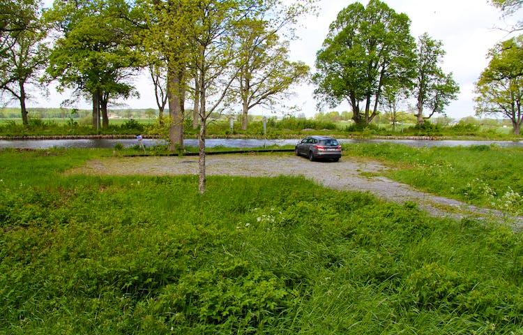 Bil parkerad på parkeringsplats invid kanalen.