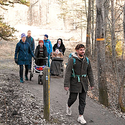 Sju personer promenerar mot fotografen. En går med rollator och en blir skjutsad i rullstol.