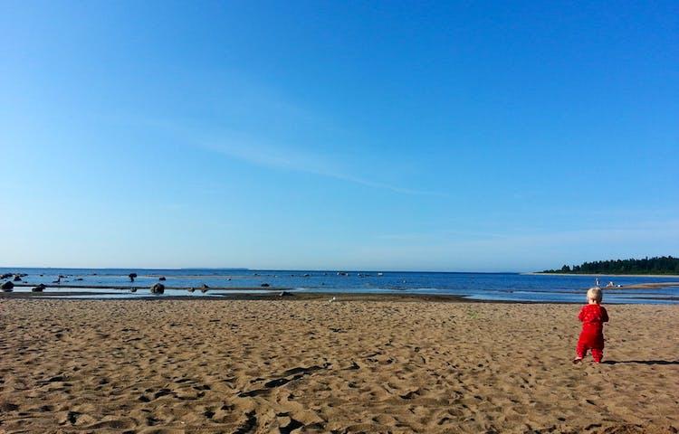 Ett litet barn går på en sandstrand vid havet.