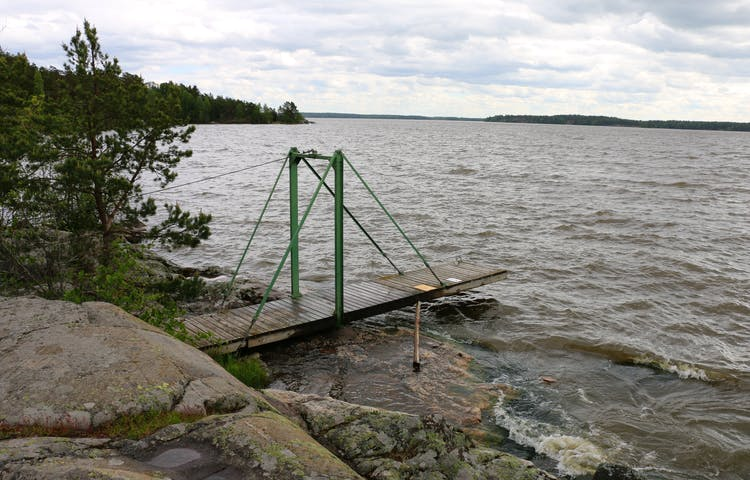 Träbrygga som går ut i vattnet från klippor.